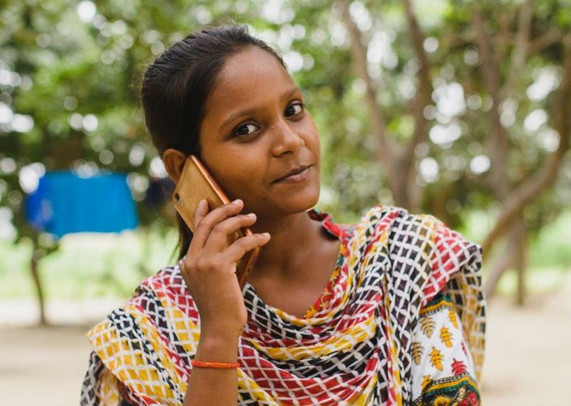 En jente snakker i mobiltelefon mens hun ser mot kamera.