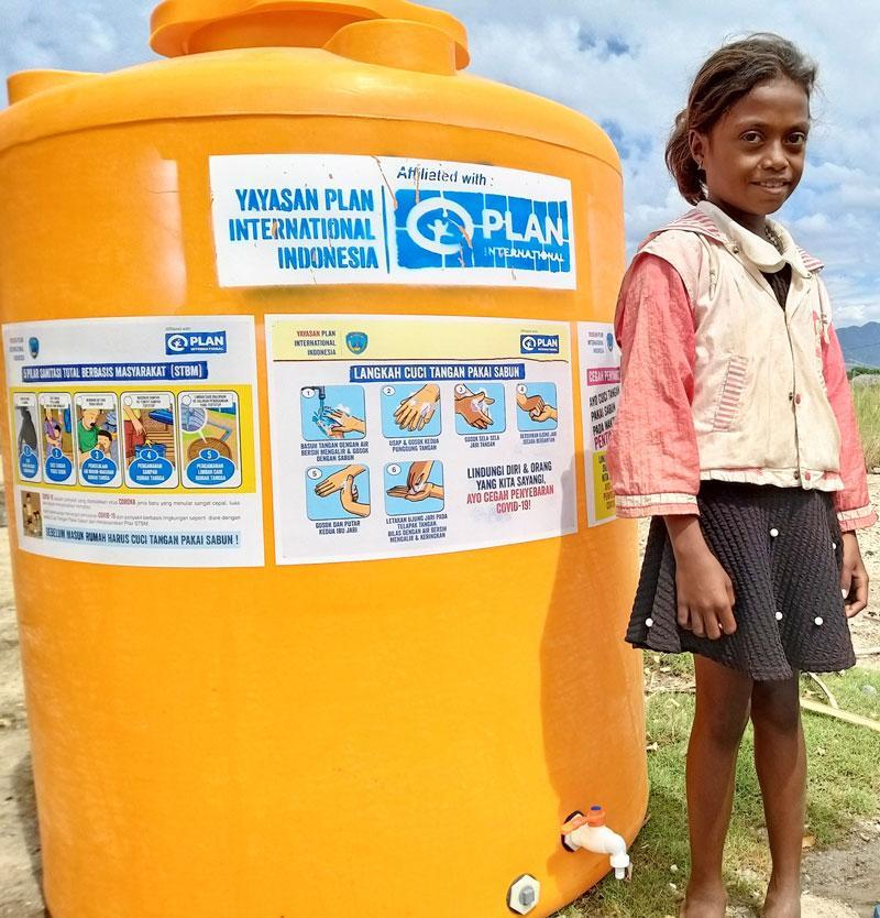 Jente står ved siden av stor vanntank for håndvask. Indonesia.
