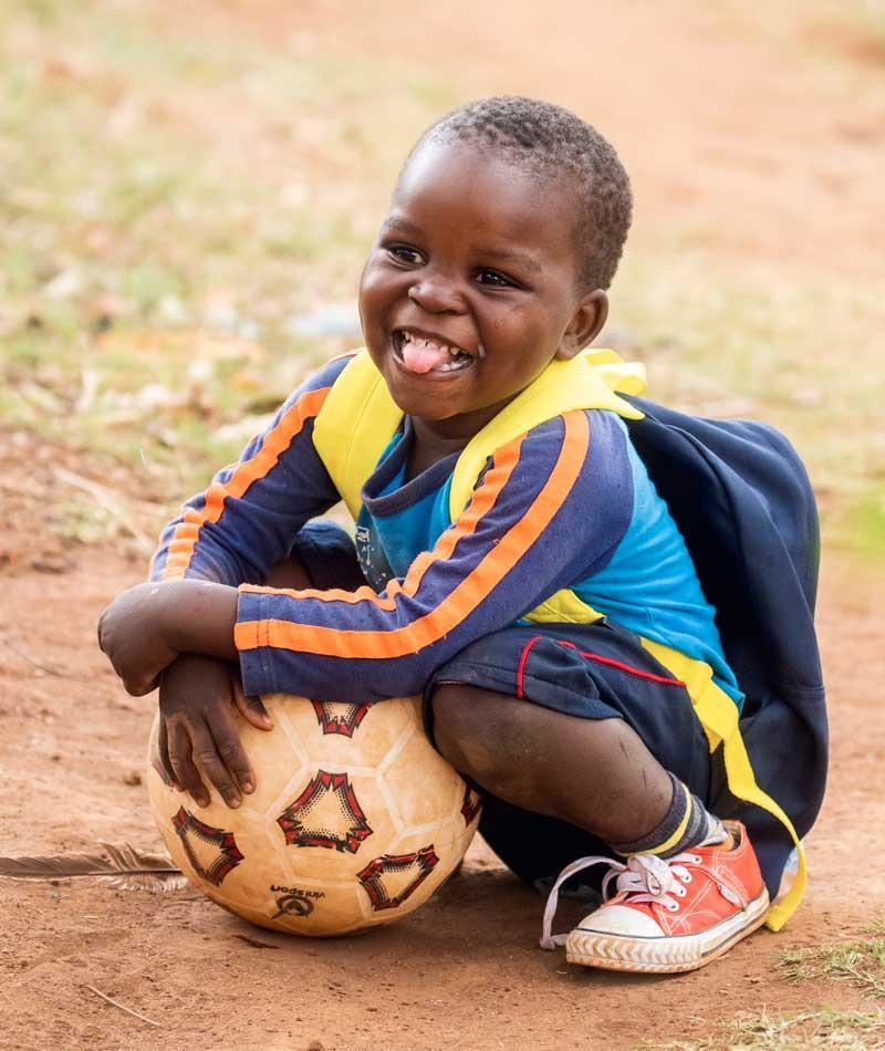 3-åring sitter på bakken og holder rundt fotball