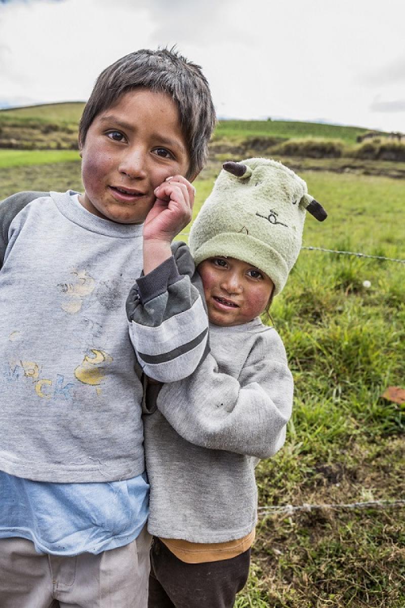 Bildet viser et søskenpar foran en gresslette; en jente på tre år og en gutt som er noen år eldre