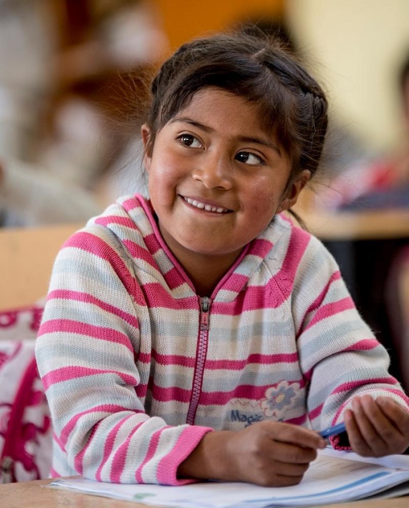 En jente sitter og smiler med en blyant i hånda