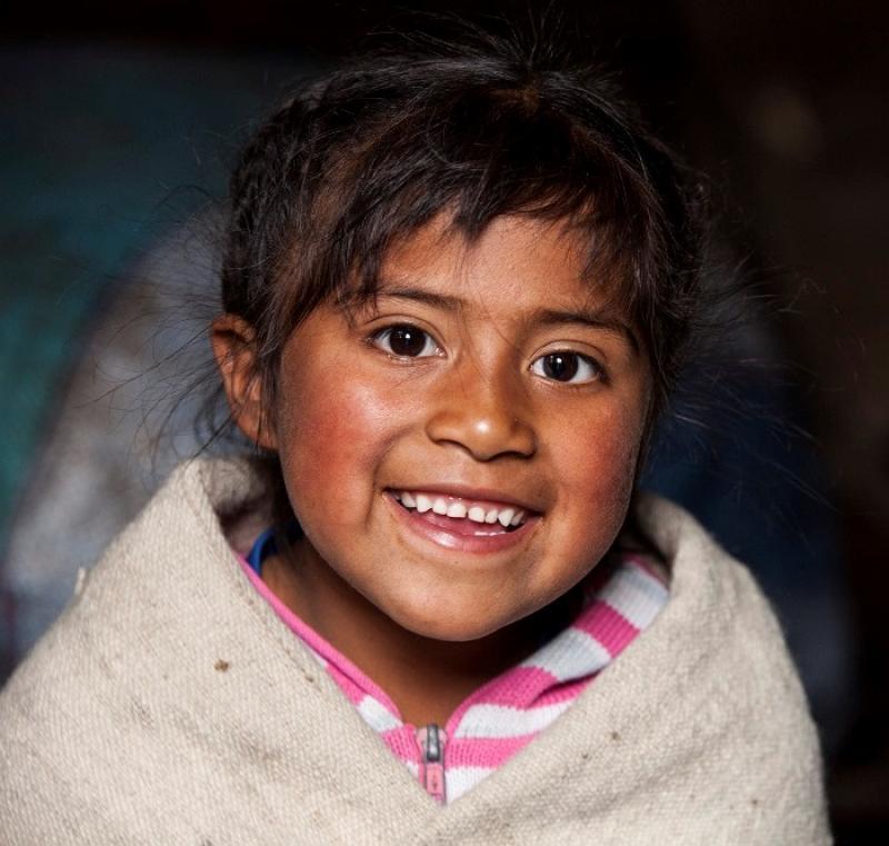 En jente, som er kledd i et beige pledd, har øyekontakt med kameraet og smiler