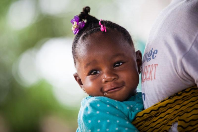 En baby festet på ryggen smiler lurt.