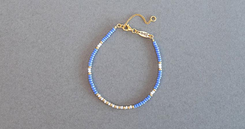Gave med mening: Perlearmbånd med glassperler i blå, gull og hvit. Sølvlås. Foto.