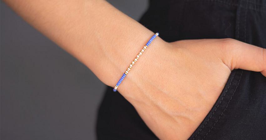 Gave med mening: Perlearmbånd med glassperler i blå, gull og hvit. Sølvlås. På hånd. Foto.