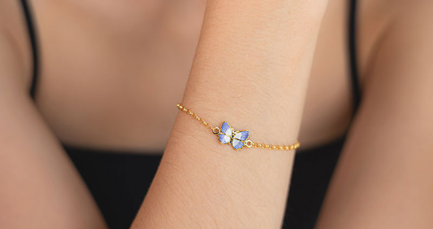 Gave med mening: Forgylt sølvarmbånd med sommerfugl i emalje. Hånd. Foto.